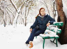 Beautiful redhead young woman sits on the bench in winter park and has a rest Royalty Free Stock Photography