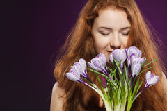 Beautiful redheaded female smelling the crocuses. Closeup of beautiful redheaded female smelling at crocuses with closed eyes Royalty Free Stock Photos