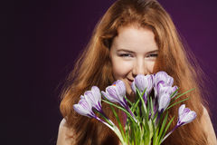 Beautiful redheaded female smelling the crocuses. Closeup of beautiful redheaded female smelling at crocuses Royalty Free Stock Image