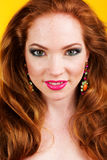 Beautiful redheaded girl with colorful earrings Stock Photos