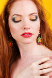 Beautiful redheaded girl with colorful earrings Royalty Free Stock Image