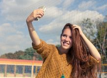 Beautiful redheaded girl doing a selfie outdoor Royalty Free Stock Photos
