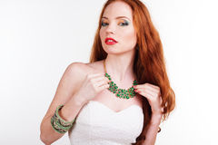 Beautiful redheaded girl with fashion makeup. Portrait of beautiful redheaded girl with fashion colorful makeup is wearing green jewelry Royalty Free Stock Image