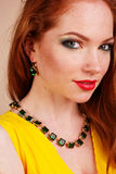 Beautiful redheaded girl with fashion makeup. Portrait of beautiful redheaded girl with fashion green jewelry Stock Image
