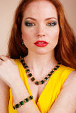 Beautiful redheaded girl with fashion makeup. Portrait of beautiful redheaded girl with fashion makeup wearing green jewelry Royalty Free Stock Photos