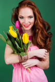 Beautiful redheaded girl with fashion makeup. Beautiful redheaded teenager girl with colorful tulips Royalty Free Stock Image