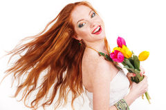 Beautiful redheaded girl with flying hair. Is holding colorful tulips Stock Images