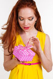Beautiful redheaded girl is holding birthday gift. Portrait of beautiful redheaded girl with fashion makeup is holding pink gift box Stock Photos