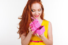 Beautiful redheaded girl is holding gift box. Portrait of beautiful redheaded girl with fashion makeup is holding pink gift box Stock Photos