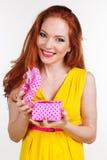 Beautiful redheaded girl is holding gift box. Portrait of beautiful redheaded girl with pink gift box Stock Photo