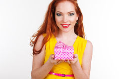 Beautiful redheaded girl is holding gift box. Portrait of beautiful smiling redheaded girl with pink gift box Royalty Free Stock Image