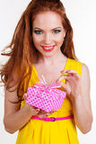 Beautiful redheaded girl is holding gift. Portrait of beautiful redheaded happy girl with fashion makeup is holding pink gift box Royalty Free Stock Images