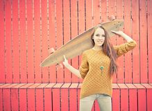 Beautiful redheaded girl holding a longboard standing near red wall Royalty Free Stock Photo