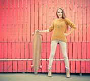 Beautiful redheaded girl holding a longboard standing near red wall Royalty Free Stock Image