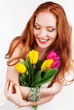 Beautiful redheaded girl is holding tulips. Beautiful redheaded girl with bouquet of colorful tulips Stock Photo