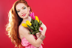 Beautiful redheaded girl is holding tulips. Beautiful redheaded girl with colorful tulips Stock Photo