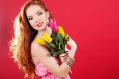 Beautiful redheaded girl is holding tulips Stock Photo