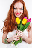 Beautiful redheaded girl is holding tulips. Beautiful redheaded girl with colorful tulips Royalty Free Stock Image