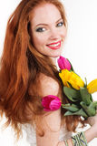 Beautiful redheaded girl is holding tulips. Beautiful redheaded girl with colorful tulips isolated on white Stock Image