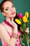 Beautiful redheaded girl is holding tulips. Beautiful redheaded fashion girl with colorful tulips Royalty Free Stock Images