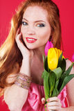 Beautiful redheaded girl is holding tulips. Beautiful redheaded girl with fashion makeup is holding colorful tulips Royalty Free Stock Photography