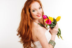 Beautiful redheaded girl is holding tulips. Beautiful redheaded girl with flying hair is holding colorful tulips Stock Image