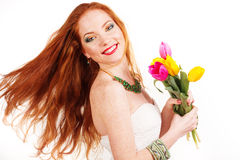 Beautiful redheaded girl is holding tulips. Beautiful redheaded girl with flying hair is holding colorful tulips isolated on white Stock Image
