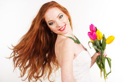Beautiful redheaded girl is holding tulips. Beautiful girl with flying red hair is holding colorful tulips Stock Images