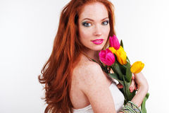 Beautiful redheaded girl is holding tulips. Beautiful redheaded girl with freckles on her face bouquet of colorful tulips Stock Photos