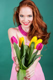 Beautiful redheaded girl is holding tulips. Beautiful redheaded girl is holding pink and yellow spring tulips Royalty Free Stock Photo