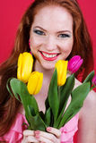 Beautiful redheaded girl is holding tulips. Portrair of beautiful redheaded girl with colorful tulips Royalty Free Stock Photo