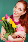 Beautiful redheaded girl is holding tulips. Beautiful smiling redheaded girl is holding colorful tulips Royalty Free Stock Photos
