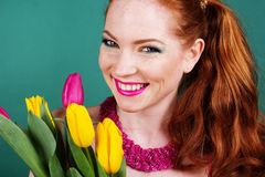 Beautiful redheaded girl is holding tulips. Beautiful redheaded smiling fashion girl with colorful tulips Stock Photos