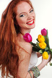 Beautiful redheaded girl is holding tulips. Beautiful redheaded smiling girl with freckles on her face bouquet of colorful tulips Royalty Free Stock Image
