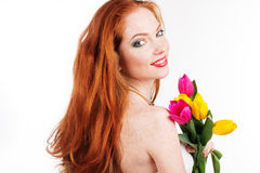 Beautiful redheaded girl is holding tulips. Beautiful redheaded smiling girl is holding tulips isolated on white Royalty Free Stock Image