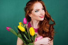 Beautiful redheaded girl is holding tulips, spring. Beautiful redheaded fashion girl with colorful tulips Stock Photos