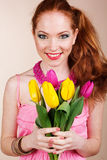 Beautiful redheaded girl is holding tulips. Beautiful redheaded girl with yellow and pink tulips Stock Photos