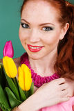 Beautiful redheaded girl is holding yellow tulips. Portrait of nice teenager redheaded girl is holding colorful tulips Stock Image