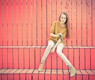Beautiful redheaded girl  in jeans sits near wall of red wooden planks Royalty Free Stock Images