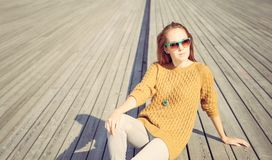 Beautiful redheaded girl in jeans sits on wooden planks Stock Photos