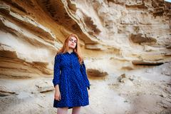 Beautiful redheaded girl standing in a blue dress in the middle of a sand quarry stock photography