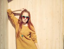 Beautiful redheaded girl in sunglasses standing near wooden wa Stock Photography