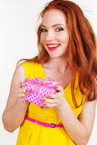 Beautiful redheaded happy girl is holding gift box Stock Photos