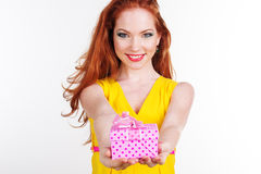 Beautiful redheaded happy girl is holding gift box Stock Photography
