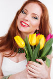 Beautiful redheaded happy girl is holding tulips. Beautiful redheaded smiling girl with freckles on her face with bouquet of colorful tulips Stock Image