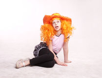 Beautiful redheaded  little girl sitting in studio. Actress, orange, hat, child on white Stock Photo