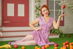 Beautiful redheaded pin up girl in pink polka dot dress and vintage stockings posing near the entrance of her home stock image