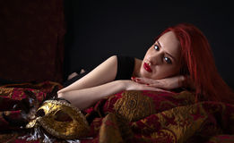 Beautiful redheaded woman with carnival mask Stock Photos