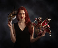 Beautiful redheaded woman with carnival mask. Beautiful redheaded woman in a black dress with carnival mask stock images