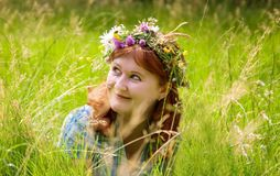 Beautiful redheaded woman in a flower wreath. Beautiful young redheaded woman in a flower wreath Royalty Free Stock Photos